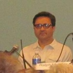 Ralph Miranda speaking while panelists look on